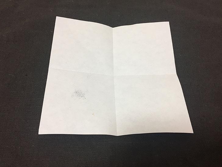 縦横半分に折り目をつけた白い面の折り紙の写真