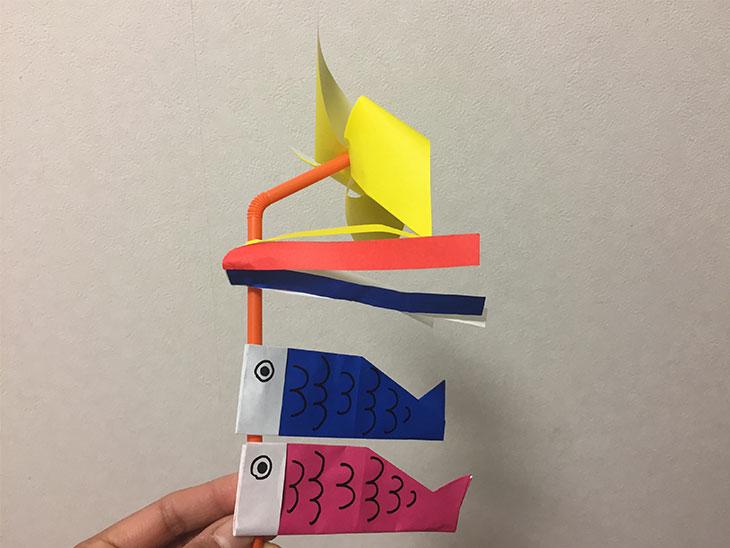 吹き流しとこいのぼりをつけた折り紙の回る風車の写真