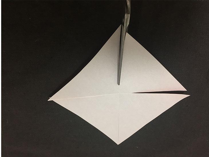 中心部分を残して折り紙の折り目を切っている写真