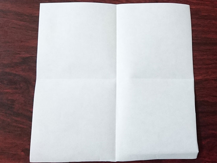 縦横に折り目をつけた白い面の折り紙の写真