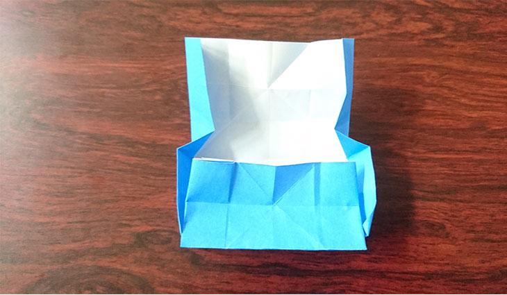 折り線に沿って箱を折りたたんでいる様子の写真