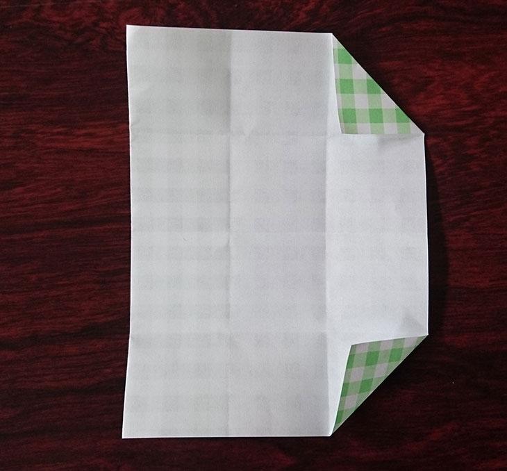 折り紙を開いて右上下の角を折り目に重ねて折った写真