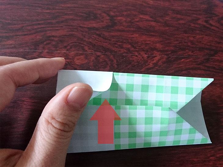 折り紙を折り線に沿って上下に折って左端を差し込む様子の写真