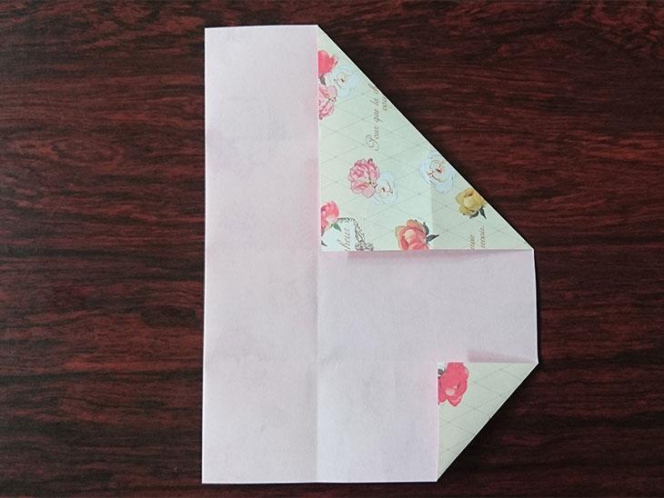 左端を折った折り紙を折り線に沿って折った写真