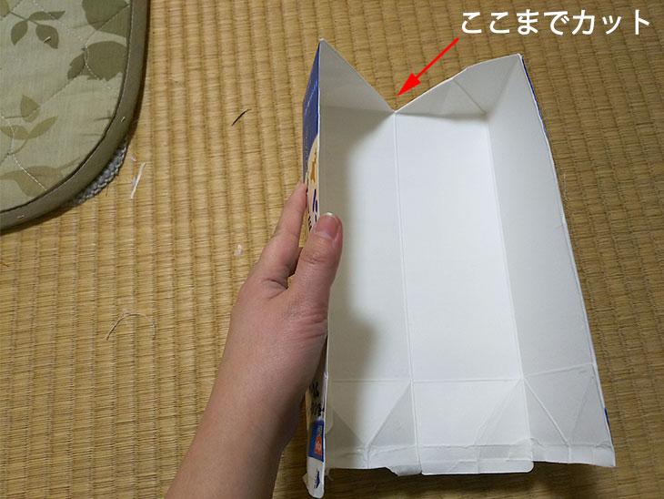 牛乳パックの底を対角線に切り開く様子