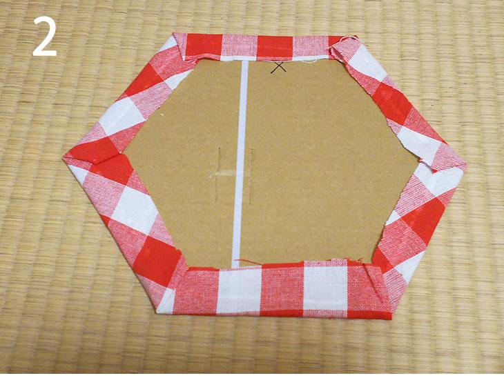ダンボールに塗ったボンドに沿って布を折り返して貼り付ける