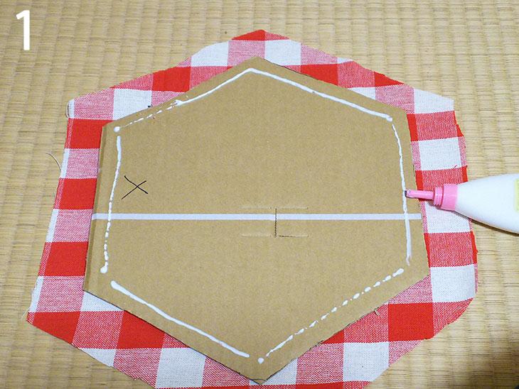 ダンボールの型に布を張るためにボンドを塗る