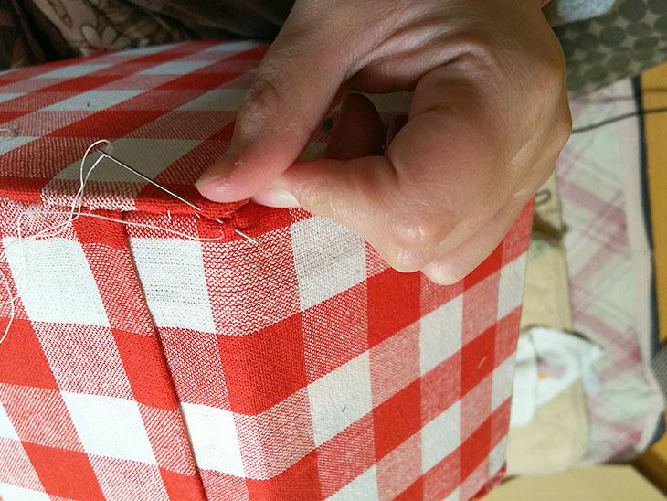 座面や底面と土台を糸と針でかがり縫いする様子