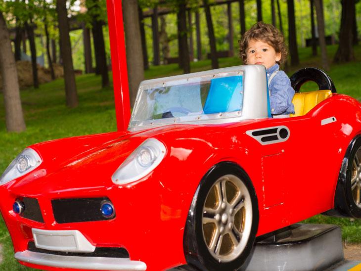 公園にある赤い車の遊具で遊んでいる男の子