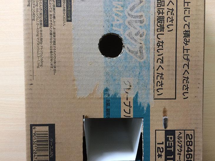 正面にペットボトルのキャップが入る穴をあけたダンボールの写真