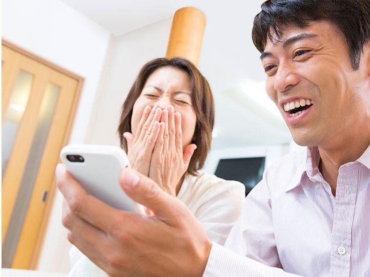 スマホを見ながら笑う夫婦