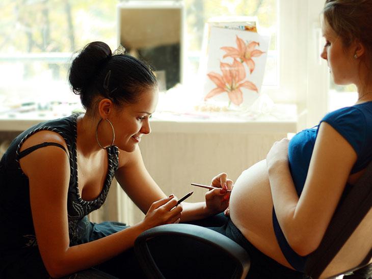 妊婦さんのお腹にベリーペイントを描いているアーティスト