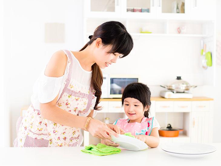 台所でお母さんを手伝うこども