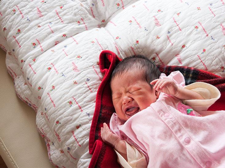 布団の上で寝起きに泣いている赤ちゃん