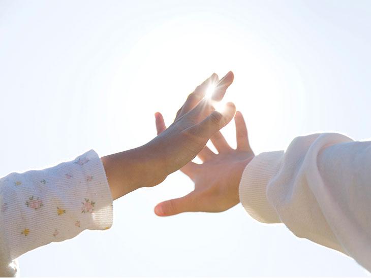 太陽の光を浴びる人の手