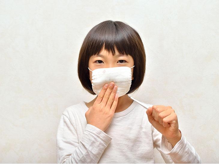 体温計を持ってマスクをする女の子