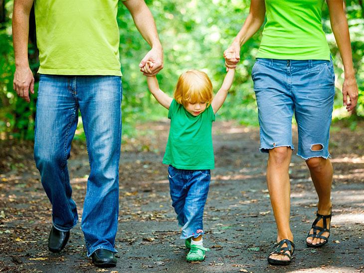 両親と一緒に歩く2歳児