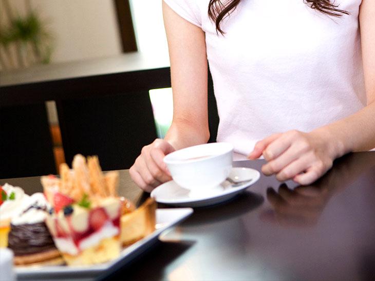 デザートとカップを持つ女性