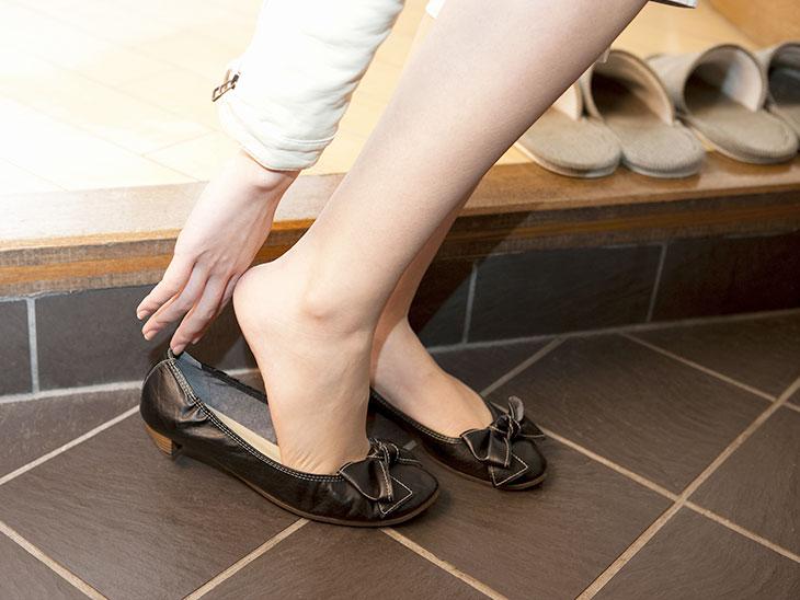 玄関で靴を履く女性