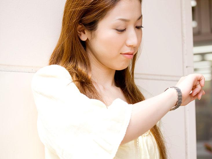 腕時計で時間を見る女性