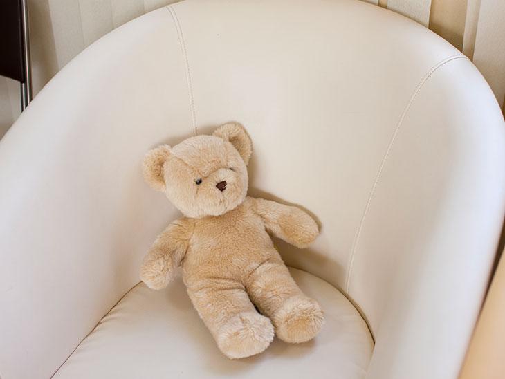 病院の待合室のイスにクマのぬいぐるみ