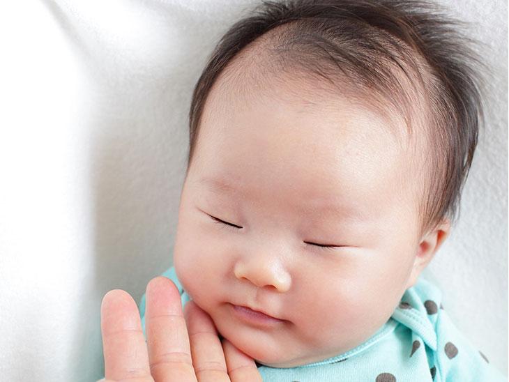 寝てる赤ちゃんの頬を触る母親の手