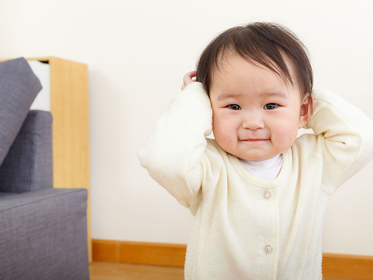 両手で耳を塞いでいる赤ちゃん