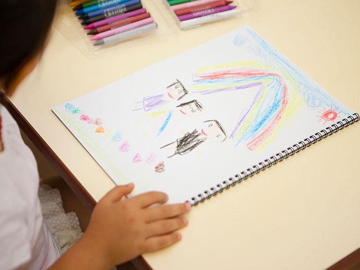 家族の絵を描いてる女の子