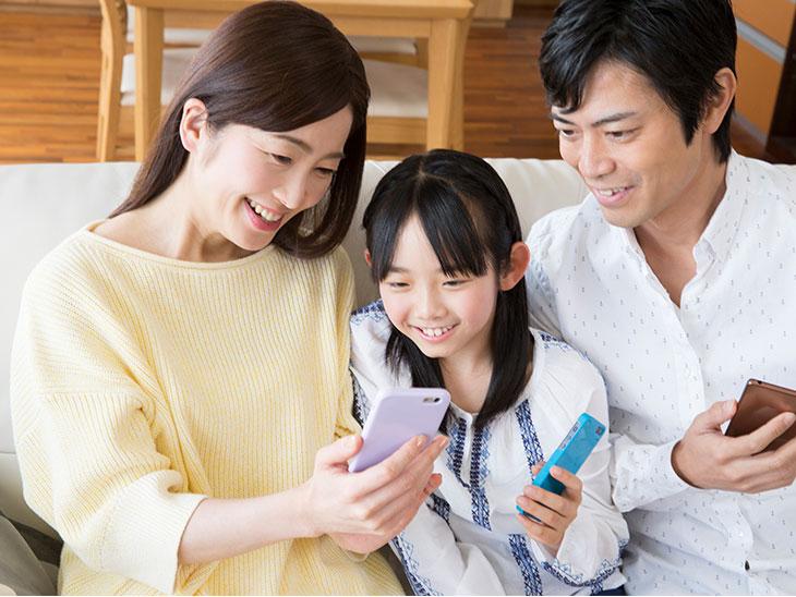 スマートフォンを見る家族