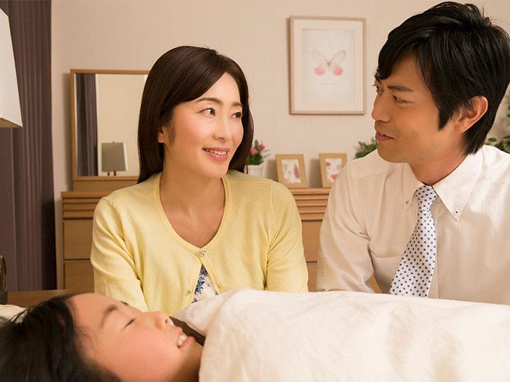 子供の寝顔を見る夫婦