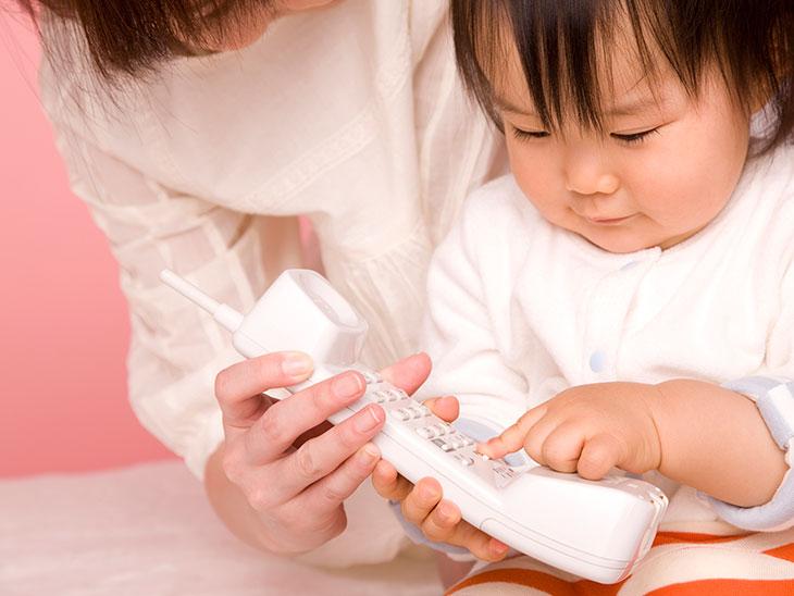 母親と電話で遊ぶ赤ちゃん