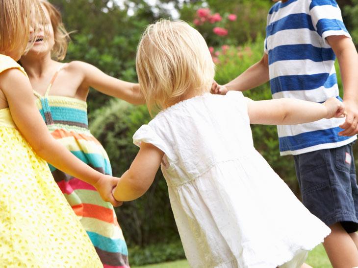 友達同士で手を繋ぎ輪になって遊んでいる子供達