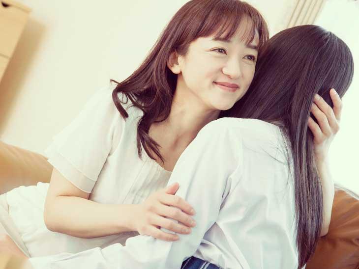 中学生の娘を抱きしめてる母親