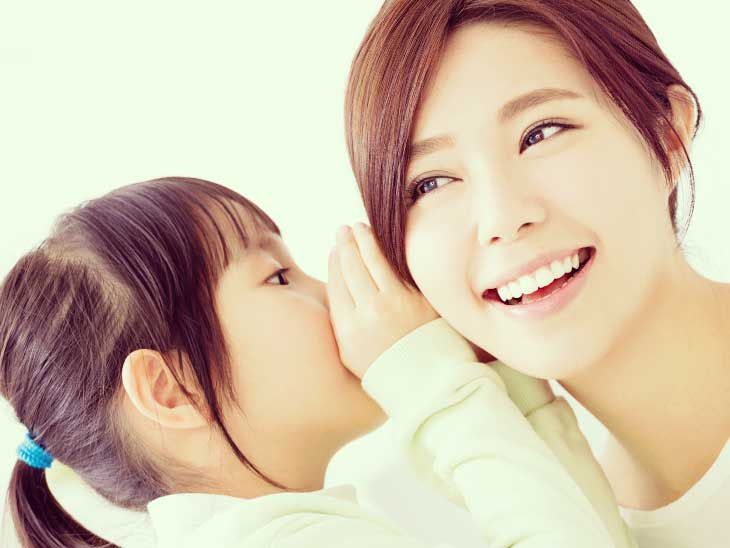 子供に耳打ちされて笑顔の母親