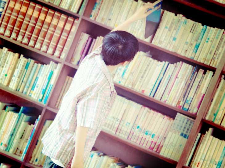 図書館で本を選んでる小学生の男の子