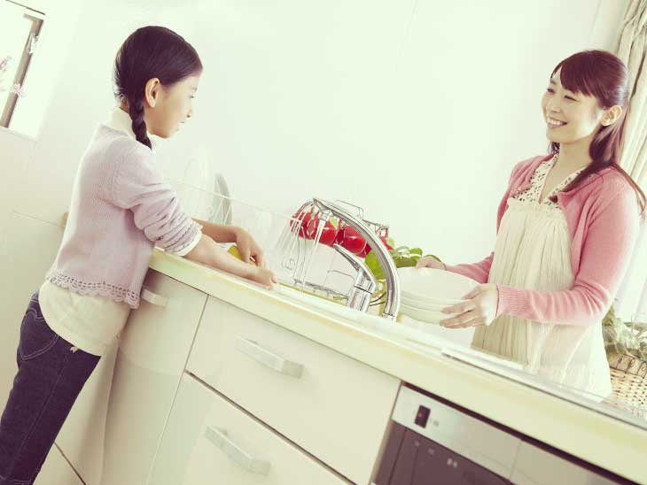 洗い物をしながら子供と笑顔で話をしているママ