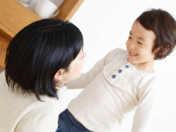 子供と目線を合わせて会話する母親