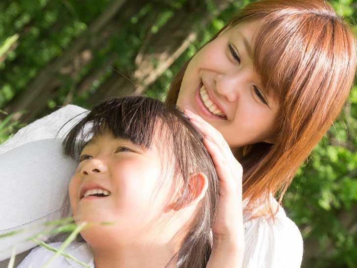 子供の頭を撫でて褒めてる母親