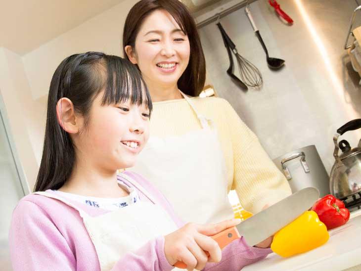 母親の料理の手伝いをしている女の子