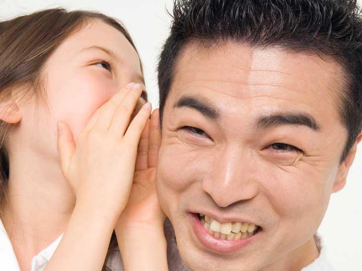 娘と内緒話をして笑顔のパパ