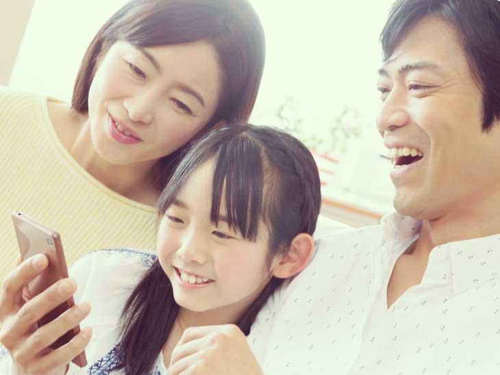 娘と奥さんと一緒にスマホを見て笑っているパパ