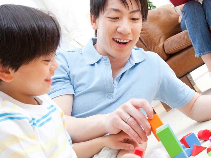 積み木で息子と遊んでいる父親