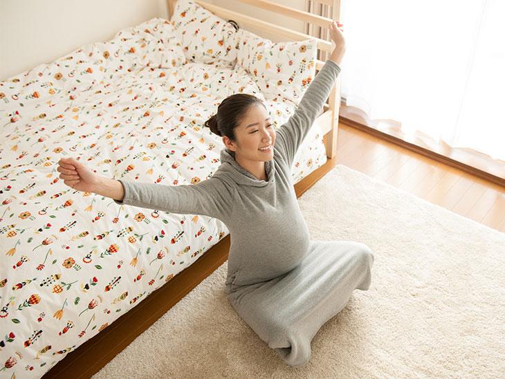 手を広げて伸びをしてる妊婦さん
