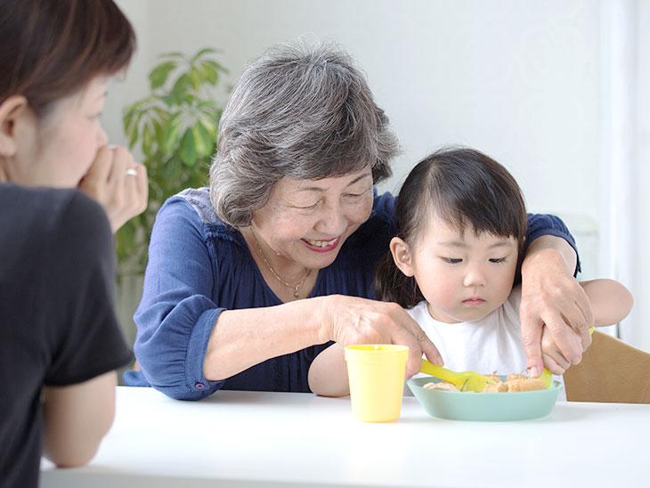 おばあちゃんに教えられてご飯を食べてる孫