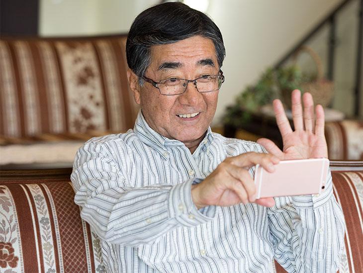 携帯のテレビ電話で孫と話をしているおじいちゃん