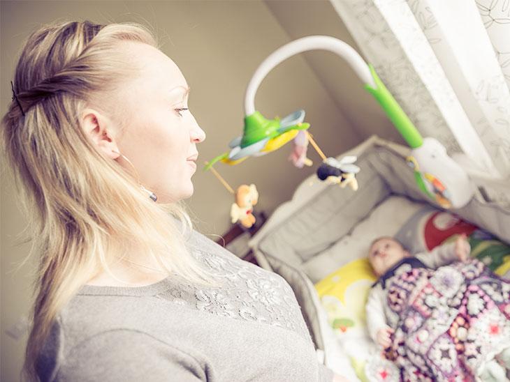 ベビーベッドに寝てる赤ちゃんを見守る母親