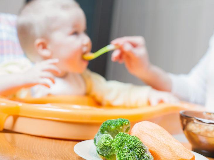 赤ちゃんにスープを食べさせる母親
