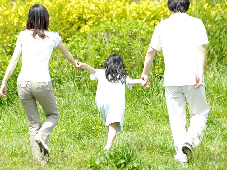 手を繋いで芝生を歩いている家族