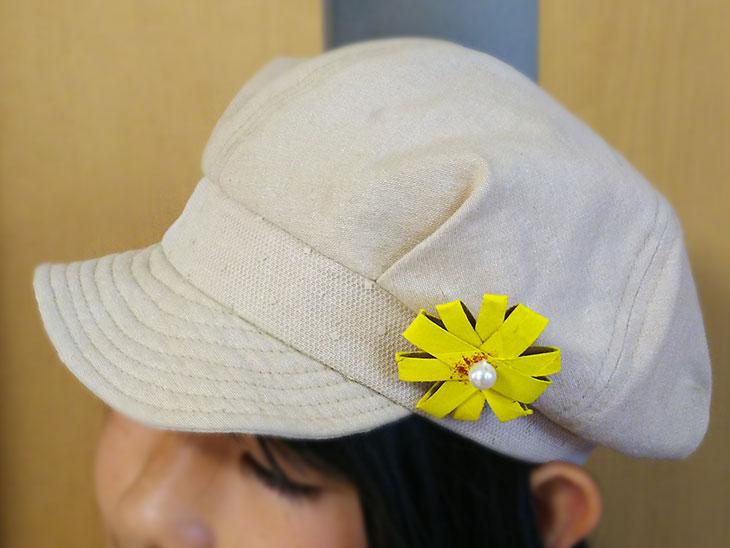 完成したラップの芯で作った花を帽子につけた写真