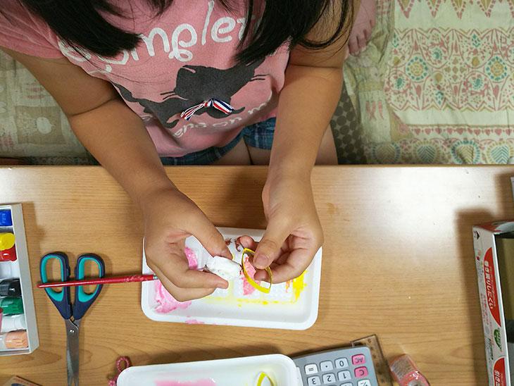 カットしたラップの芯に子供が色を付ける様子